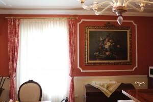 immagine rappresenta una cornice in gesso su parete rossa che adorna un quadro floreale